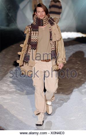 Iceberg Menswear Milan A W Dark blonde male long hair wearing a khaki coloured open jacket over a V neck jumper, khaki - Stock Photo