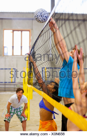 Friends having fun playing indoor beach volleyball - Stock Photo