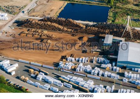 Aerial view of stacked tree trunks and warehouses in timber yard - Stock Photo