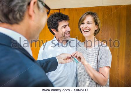 Estate agent handing keys to mature couple in new house - Stock Photo