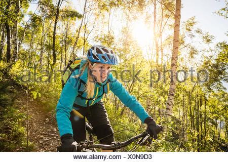 Young woman riding mountain bike through woods, Lake Como, Italy - Stock Photo