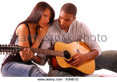 young, dark skinned couple nestling to each other while the man plays on the guitar - Stock Photo