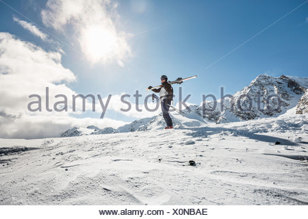 Mid adult man standing on top of mountain with skis, Corvatsch, Switzerland - Stock Photo