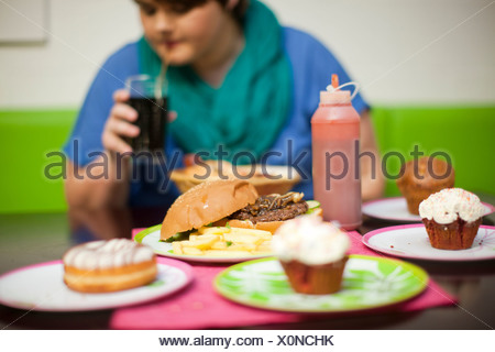 Young woman in cafe with table of food - Stock Photo