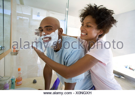 Young couple in bathroom, woman putting shaving foam on man's face, smiling - Stock Photo