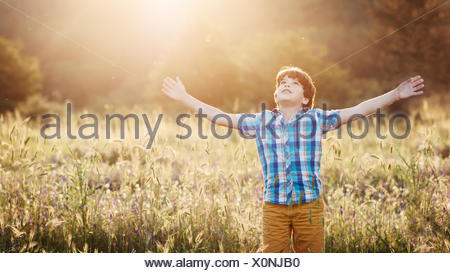 Boy (8-9) in meadow with arms outstretched looking up - Stock Photo