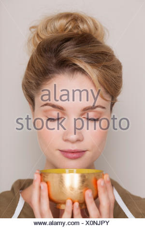 Woman holding a bowl of green tea - Stock Photo