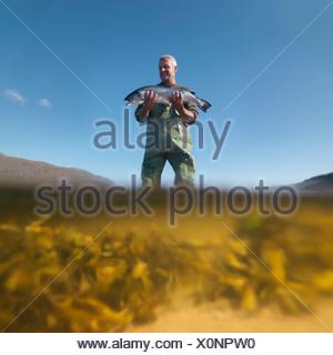 Fisherman with salmon in still lake - Stock Photo