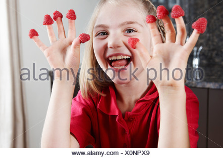 Girl with raspberries on fingers - Stock Photo