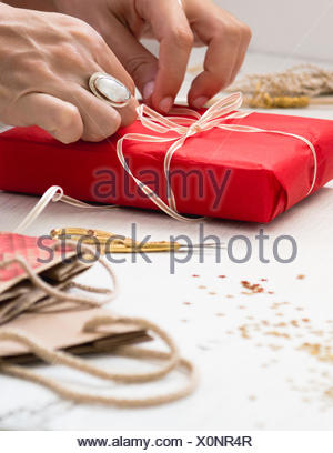 Cropped Image Of Hand Tying Ribbon On Gift At Table - Stock Photo