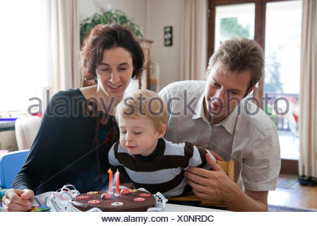 young family celebrating their sons second birthday - Stock Photo