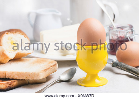 Breakfast with eggs and toast served with jam and butter on a white table cloth - Stock Photo