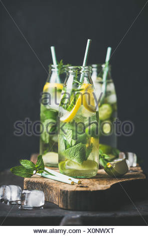 Citrus fruit and herbs infused sassi water for detox, healthy eating or dieting in glass bottles with straws, dark background, selective focus. Clean - Stock Photo