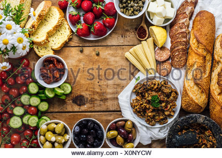 Olive tapenade, sausages, baby corns, french baguette, cheese, capers, strawberries, corn bread slices, sun-dried tomatoes, cherry tomatoes and cucumb - Stock Photo
