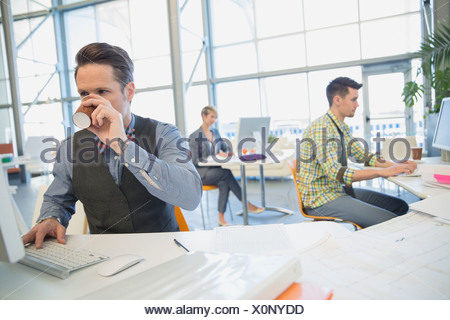 Businessman drinking coffee at desk in office - Stock Photo