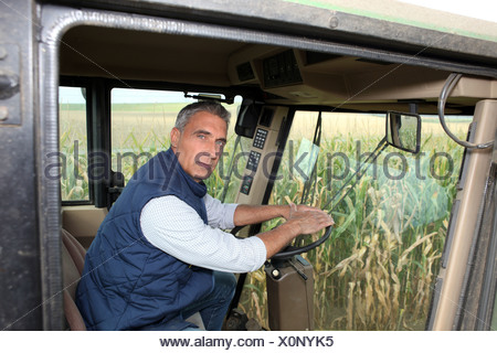 Farmer driving a tractor - Stock Photo