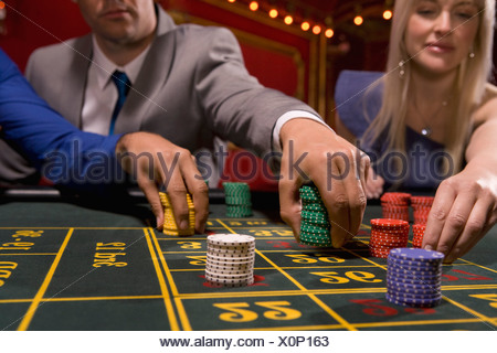 People placing bets with gambling chips - Stock Photo