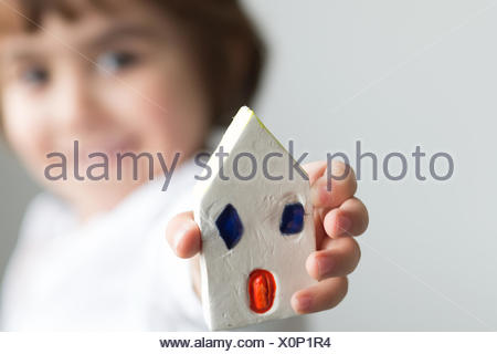 Boy showing off his handmade house - Stock Photo