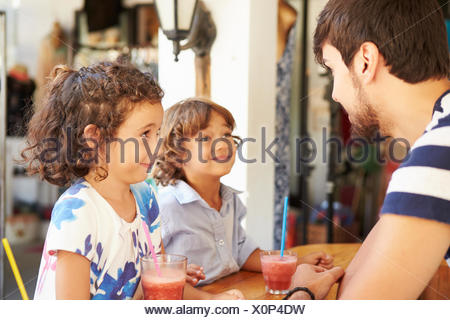 Children Drinking Fruit Smoothies In Restaurant - Stock Photo