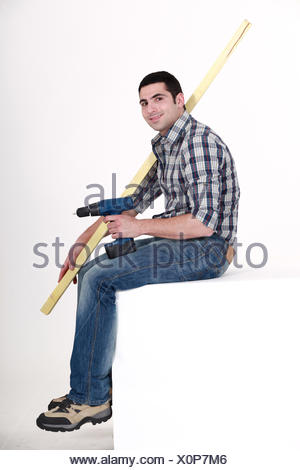 Man sat with power drill and length of wood - Stock Photo
