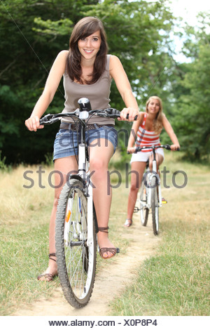 Two teenage girls on bikes in the forest - Stock Photo