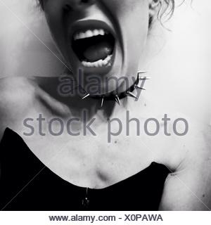 Midsection Of Young Woman Wearing Spiked Choker With Mouth Open Against White Background - Stock Photo