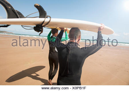 Man and teenage boy carrying surfboards on beach - Stock Photo