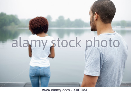 Portrait of young couple by lake, rear view - Stock Photo