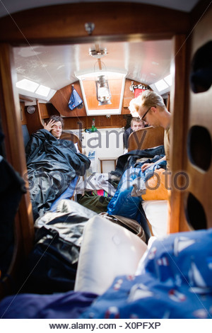 Young men waking up in a sailing-boat, Sweden. - Stock Photo
