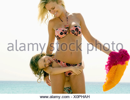 Woman and young girl being playful at the beach smiling. - Stock Photo