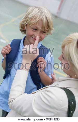 Mother sending son off to school - Stock Photo