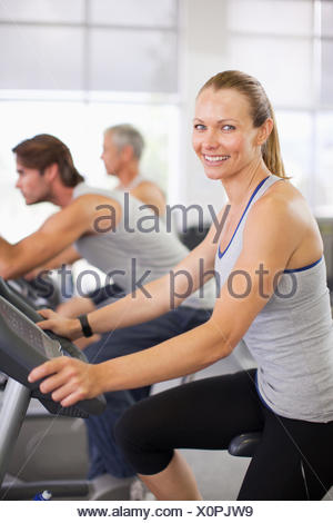 Portrait of smiling woman on exercise machine in gymnasium - Stock Photo