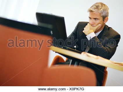 Businessman, hand to chin, working on computer - Stock Photo