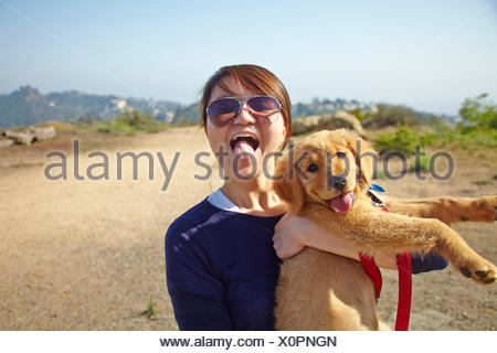 Young woman holding labrador puppy, tongues out - Stock Photo