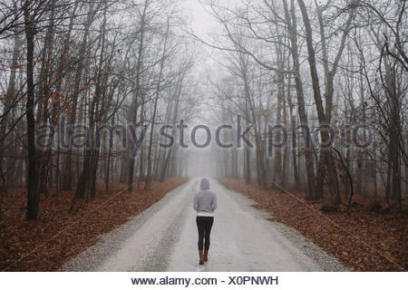 USA, Tennessee, Rear view of woman walking along road - Stock Photo