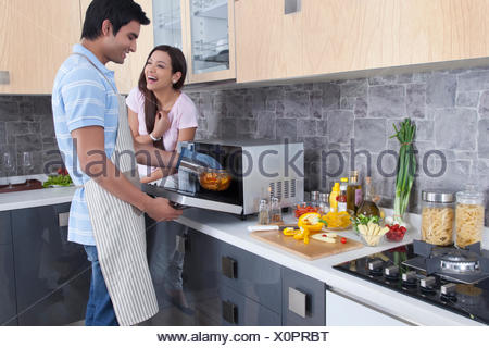 Happy Indian couple preparing food in kitchen - Stock Photo
