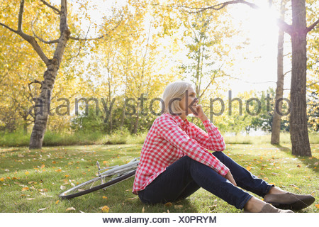 Thoughtful woman sitting in park - Stock Photo