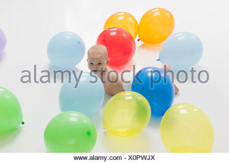 Baby laying on floor with balloons - Stock Photo
