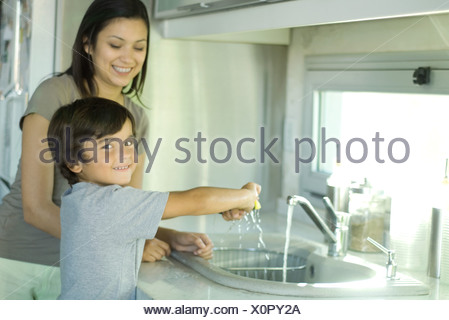 Boy helping mother wash dishes, looking over shoulder at camera - Stock Photo