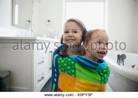 Portrait enthusiastic sisters wrapped a towel bathroom - Stock Photo