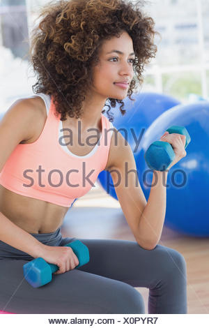 Young woman exercising with dumbbells in gym - Stock Photo