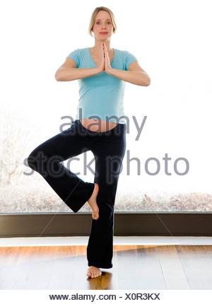 pregnant woman doing yoga exercises - Stock Photo