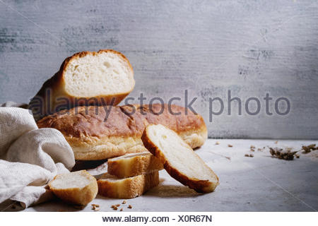 Homemade white wheat bread whole and slice served with flour and wheat grain seeds, white linen towel over gray texture kitchen table. - Stock Photo