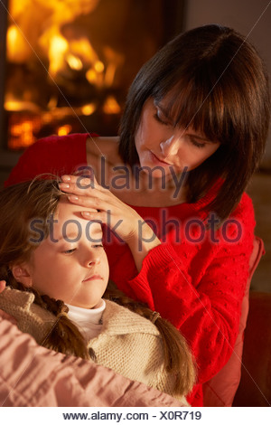 Mother Comforting Sick Daughter On Sofa By Cosy Log Fire - Stock Photo