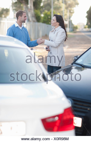 Drivers of car accident shaking hands - Stock Photo
