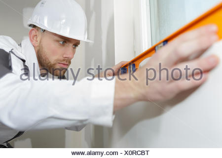 plasterer checking if walls are straight - Stock Photo