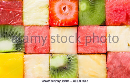 Background texture of diced tropical summer fruit cut in cubes and arranged in rows for a seamless pattern with watermelon, strawberry, kiwifruit, pineapple and melon - Stock Photo