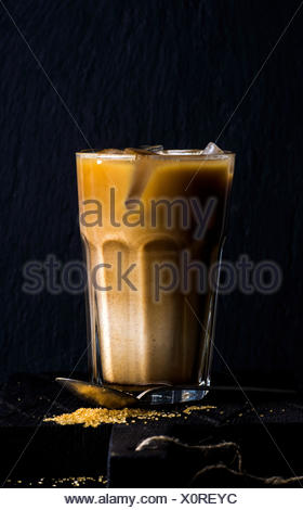 Iced coffee with milk in a tall glass, black background, selective focus - Stock Photo