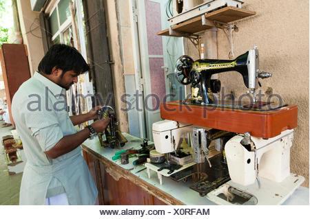 A sewing machine repairman at work at the souk in Nizwa. - Stock Photo