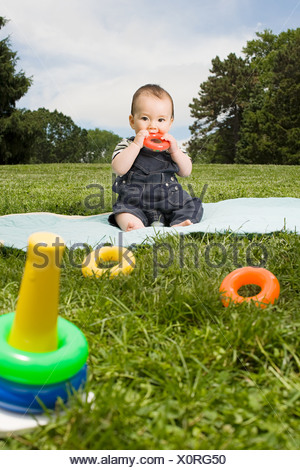 Baby boy in park with toy rings - Stock Photo